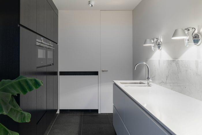Luxury kitchen with white worktops, dark grey floors and cupboards