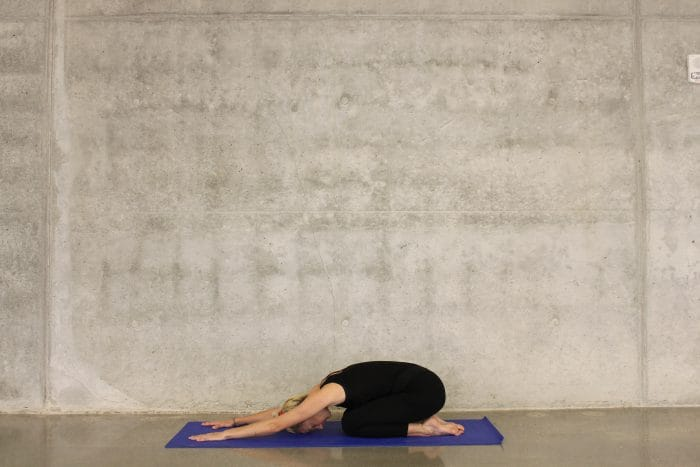 woman positioned on yoga mat
