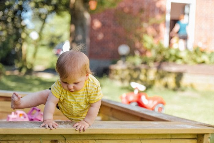 baby climbing out of sand pit